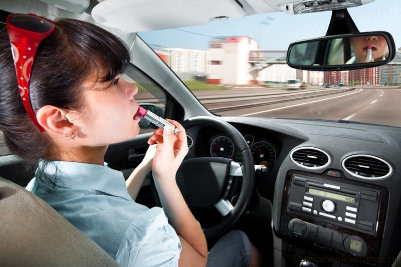 женщина за рулём красит губы
